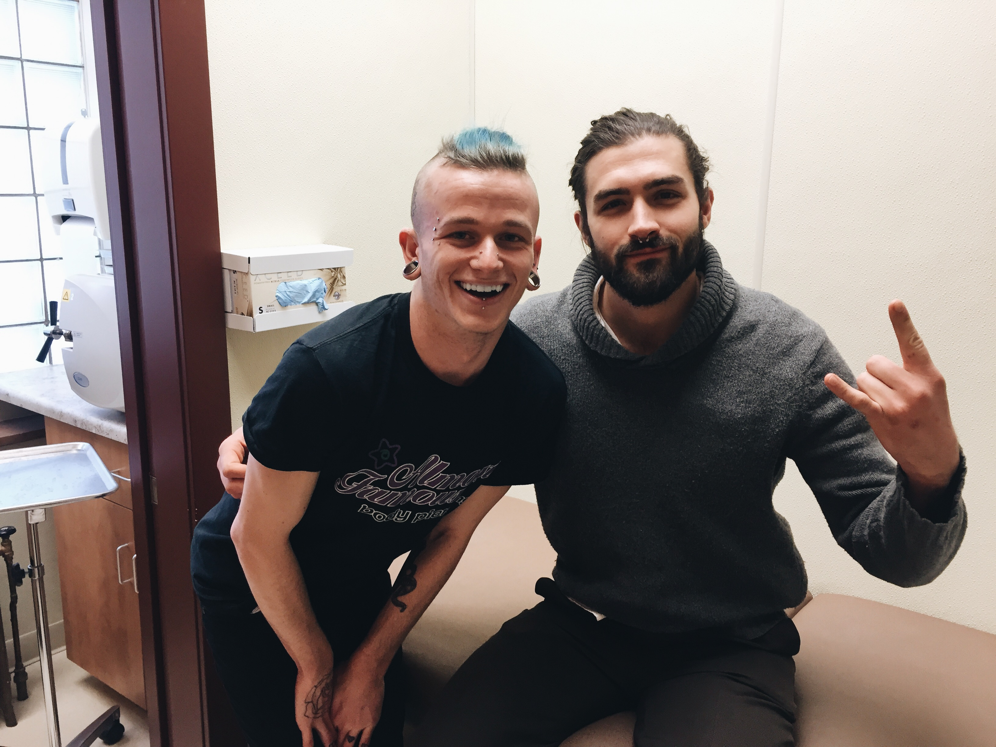 piercing technician poses with newly pierced person