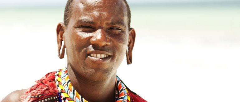 Portrait of young Masai man posing on beach with large piercing holes in his ear lobes